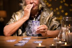 Fortune teller reading tarot card. Close up of aged fortune teller reading tarot card meaning Royalty Free Stock Photo