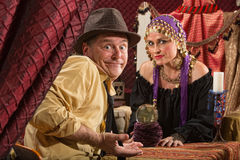Fortune Teller and Skeptical Man. Fortune teller in head scarf with skeptical customer and crystal ball stock image