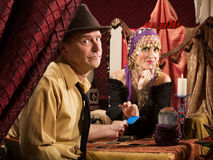 Fortune Teller Takes Credit Card. Beautiful fortune teller receiving payment from frowing man Royalty Free Stock Photo