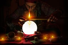 Fortune teller witch holding candle. Fortune teller witch holding burning candle above crystal ball Stock Photos