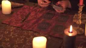 Fortune teller woman in dark room with lots of candles guesses on a tarot card deck using card layout. 4k UHD stock video footage
