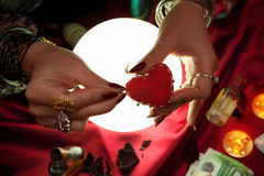 Fortune teller woman holding handmade heart with pin. For witchcraft Stock Photos