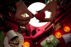 Fortune teller woman holding little heart for witchcraft. Fortune teller woman holding little heart and little pin for witchcraft Royalty Free Stock Photo