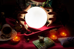 Fortune teller woman looking at crystal ball with her hands arou. Gypsy fortune teller woman looking at crystal ball with her hands around crystal ball Stock Photo