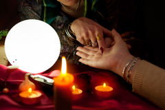 Fortune teller woman point her finger to another woman palm. Palm reading stock photo