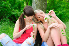 Fortune-telling girls. Pretty girls fortune-telling on camomiles Stock Images