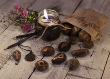 Fortune telling still life with black candles and ancient runes on stones Royalty Free Stock Image