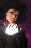 Fortune telling woman. Mysterious fortune telling woman with glowing crystal ball looking at the camera Stock Photo
