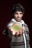 Fortuneteller With Crystal Ball. Caucasian male fortuneteller holds glowing crystal ball Royalty Free Stock Images