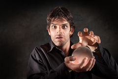 Fortuneteller With Crystal Ball. Fortuneteller gazes crystal ball over maroon background Stock Photography