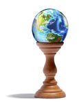 Fortuneteller glass globe on a wooden plinth. Fortuneteller glass globe showing the continents and oceans of the Earth on a wooden plinth or stand over a white Stock Image