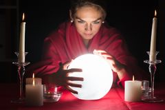 Fortuneteller Holding Hands Around A Glowing Ball. Beautiful Young Fortuneteller Holding Hands Around A Glowing Ball stock image