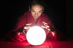 Fortuneteller Holding Hands Around A Glowing Ball. Beautiful Young Fortuneteller Holding Hands Around A Glowing Ball stock images