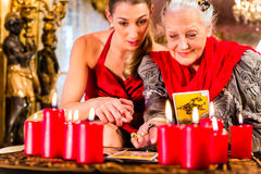Fortuneteller laying Tarot cards with client. On pentagram, candles are burning Stock Image