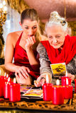 Fortuneteller laying Tarot cards with client. On pentagram, candles are burning Stock Images