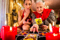 Fortuneteller laying Tarot cards with client. On pentagram, candles are burning Royalty Free Stock Photography