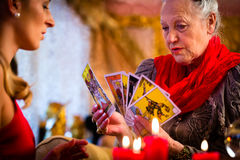 Fortuneteller laying Tarot cards with client. On pentagram, candles are burning Stock Photos