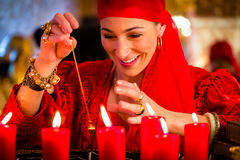 Fortuneteller during pendulum session. Female Fortuneteller or esoteric Oracle, sees in the future by dowsing her pendulum during a Seance to interpret them and Royalty Free Stock Photography