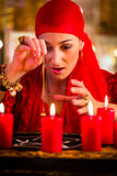 Fortuneteller during pendulum session. Female Fortuneteller or esoteric Oracle, sees in the future by dowsing her pendulum during a Seance to interpret them and Royalty Free Stock Photo