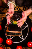 Fortuneteller during Seance with crystal ball. Female Fortuneteller or esoteric Oracle, sees in the future by looking into their crystal ball during a Seance to Stock Images