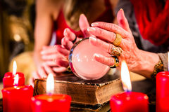 Fortuneteller during Seance with crystal ball. Female Fortuneteller or esoteric Oracle, sees in the future by looking into their crystal ball during a Seance to Royalty Free Stock Photos