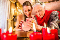 Fortuneteller during Seance with crystal ball. Female Fortuneteller or esoteric Oracle, sees in the future by looking into their crystal ball during a Seance to Stock Photography