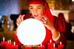 Fortuneteller at Seance or session with Crystal ball. Female Fortuneteller or esoteric Oracle, sees in the future by looking into their crystal ball during a Stock Image