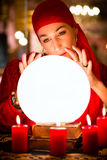 Fortuneteller at Seance or session with Crystal ball. Female Fortuneteller or esoteric Oracle, sees in the future by looking into their crystal ball during a Royalty Free Stock Photography