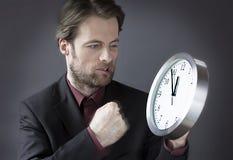 Kontorsarbetaren under tid pressar att stansa tar tid på med hans näve arkivfoto