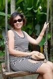 Forty år gammal kvinna som kopplar av i trädgård arkivfoton