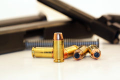 Forty caliber bullets. A collection of forty caliber bullets with a disassembled pistol in the back ground Stock Photo