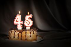 Forty five years anniversary. Birthday chocolate cake with white burning candles in the form of number Forty five. Dark background with black cloth royalty free stock photo