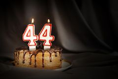 Forty four years anniversary. Birthday chocolate cake with white burning candles in the form of number Forty four. Dark background with black cloth royalty free stock photos