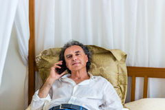 Forty on phone on four poster bed Royalty Free Stock Photography