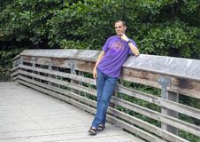 Forty-two yearold Caucasian man posing on a wooden bridge in the Washington Park Arboretum, Seattle, Washington. Pictured is a forty-two year-old Caucasian man royalty free stock images