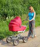 Forty-year mother walks with a baby carriage Stock Photography