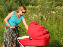 Forty-year mother walks with a baby carriage Royalty Free Stock Photo
