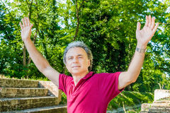 Forty years adult raising arms on medieval steps Stock Photo