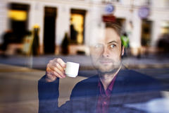 Businessman drinking espresso coffee in the city cafe royalty free stock photography