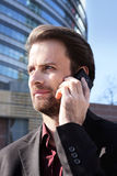 Businessman outside office talking on a mobile phone Stock Images