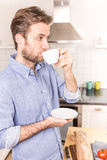 Forty years old caucasian man drinking coffee in the kitchen Stock Photography