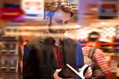 Elegant man standing inside bookstore reading a book Royalty Free Stock Image