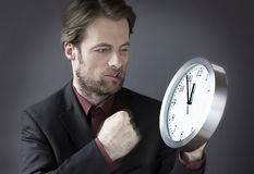 Office worker under time pressure punching clock with his fist Stock Photo