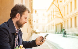Forty years old man looking at a mobile phone - city. Forty years old caucasian man looking at a mobile phone. Street and city buildings as background royalty free stock photography