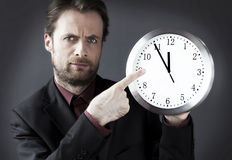 Demanding boss with a pointing finger on a clock. Forty years old strict demanding boss with a pointing finger on a clock - indicates a deadline hour Stock Image