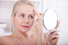 Forty years old woman looking at wrinkles in mirror. Plastic surgery and collagen injections. Makeup. Macro face. Selective focus. On the face Royalty Free Stock Image