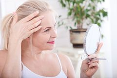 Forty years old woman looking at wrinkles in mirror. Plastic surgery and collagen injections. Makeup. Macro face. Selective focus Stock Photos