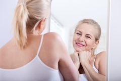 Forty years old woman looking at wrinkles in mirror. Plastic surgery and collagen injections. Makeup. Macro face royalty free stock image