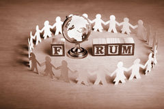 Forum. Word 'Forum' made of alphabet wooden block and a globe surrounded by paper dolls Stock Photo