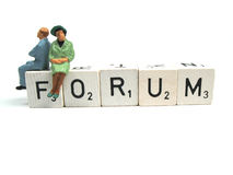 Forum. Two figurines sitting on the word forum Royalty Free Stock Photos